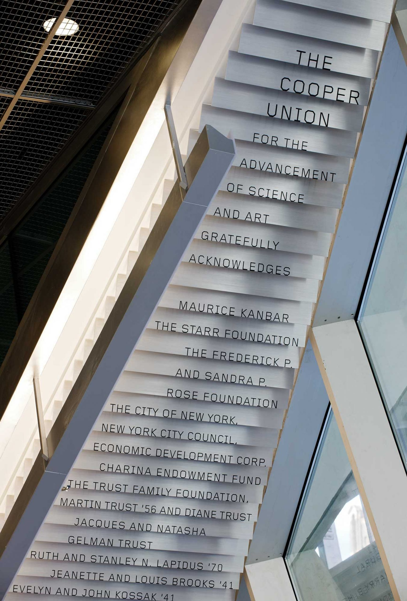 Donor signage cascades down the underside of a lobby staircase.
